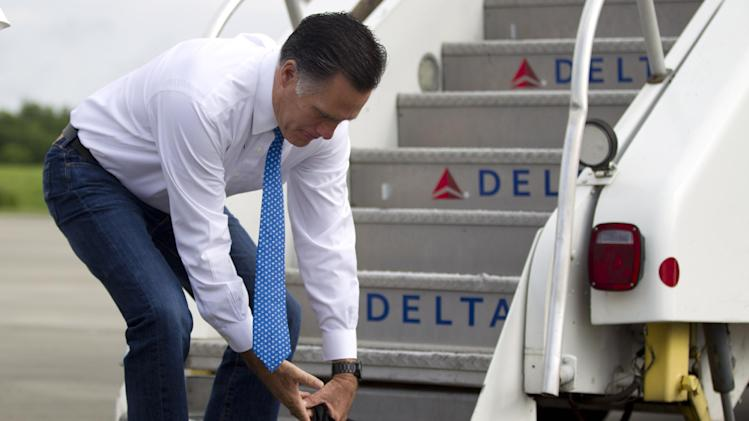 Republican presidential candidate, former Massachusetts Gov. Mitt Romney grabs his bag after arriving at Louis Armstrong New Orleans International Airport in New Orleans, Tuesday, Aug. 21, 2012, prior to departing for fundraising events in Texas .  (AP Photo/Evan Vucci)
