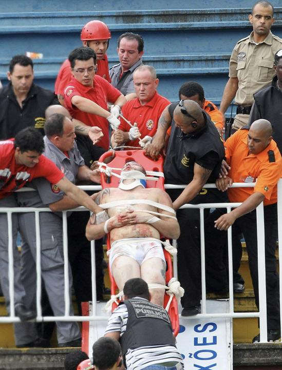 Paramedics use a stretcher to carry an injured Atletico Paranaense fan after clashes between fans of Vasco da Gama and Atletico Paranaense during their Brazilian championship match in Joinville