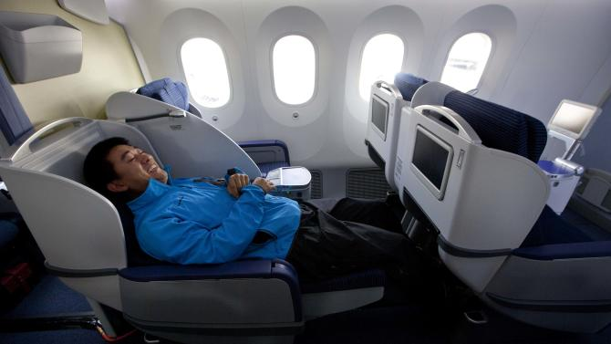Kang Kang of China Central TV sits in the reclining seat as the news media tour the second Boeing Co. 787 to be delivered to All Nippon Airways (ANA) at the assembly plant in Everett, Wash. on Sunday, Sept. 25, 2011. ANA is the first customer to take delivery of the 787. (AP Photo/John Froschauer)