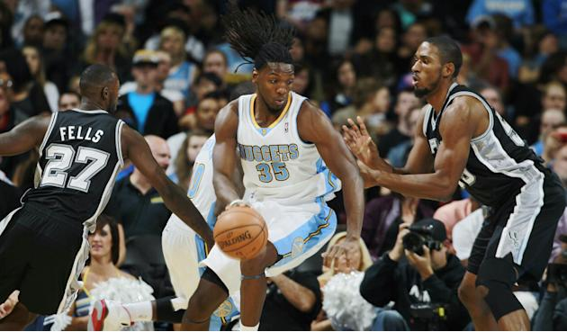 Denver Nuggets forward Kenneth Faried, center, drives the lane for a shot as San Antonio Spurs forward Courtney Fells, left, and center Marcus Cousins cover in the fourth quarter of the Nuggets' 98-94