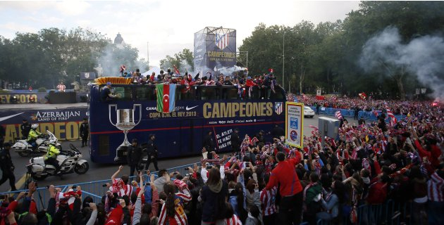 Atletico Madrid's players wave to fans from top of bus as they arrive to celebrate team's victory against Real Madrid after their Spanish King's Cup final in central Madrid