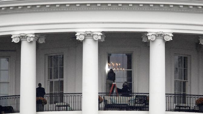 FILE - This Nov. 16, 2011 file photo shows law enforcement officers photographing a window at the White House in Washington, as seen from the South Lawn. A bullet hit an exterior window of the White House and was stopped by ballistic glass, the Secret Service said. An additional round of ammunition was found on the White House exterior. The bullets were found Tuesday morning. An Idaho man who pleaded guilty to shooting at and hitting the White House is set to be sentenced. Prosecutors say Oscar Ramiro Ortega-Hernandez should spend 27 years in prison for the 2011 shooting. His sentencing is scheduled for Monday afternoon. No one was injured, but prosecutors say Ortega-Hernandez hit the executive mansion about eight times and did nearly $100,000 in damage. (AP Photo/Haraz N. Ghanbari, File)