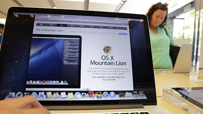 A customer looks at the new OS X Mountain Lion operating system at an Apple store in Palo Alto, Calif., Wednesday, July 25, 2012. Apple Inc. released its new operating system for Mac computers on Wednesday, with features borrowed from mobile devices and a tighter integration with online file storage. Dubbed Mountain Lion, the new software narrows the gap between the PC and phone software packages, making Mac personal computers work more like iPhones and iPads. (AP Photo/Paul Sakuma)