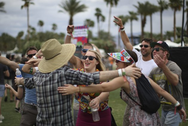 People celebrate after getting through the entrance gates of the Coachella Valley Music and Arts Festival in Indio