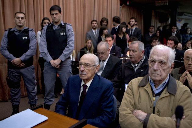 Former dictators Jorge Rafael Videla, second from right, and Reynaldo Bignone, right, wait to listen the verdict of Argentina's historic stolen babies trial in Buenos Aires, Argentina, Thursday, July