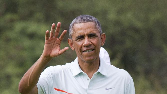 President Barack Obama waves at the traveling press as he plays golf with Malaysian Prime Minister Najib Razak Wednesday, Dec. 24, 2014, on the Marine Corps Base Hawaii's Kaneohe Klipper Golf Course in Kaneohe, Hawaii during the Obama family vacation. (AP Photo/Jacquelyn Martin)