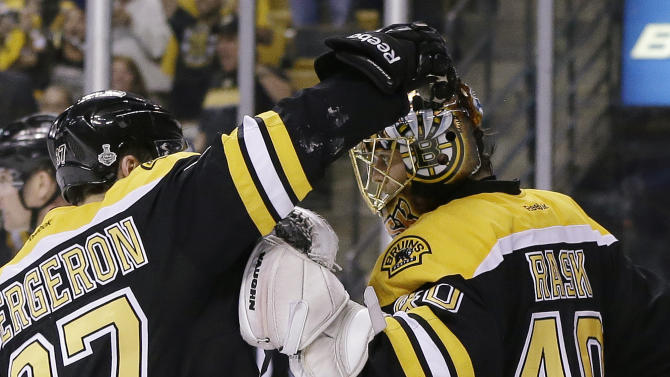 Boston Bruins center Patrice Bergeron (37) congratulates Boston Bruins goalie Tuukka Rask (40), of Finland, on his shutout to beat the Chicago Blackhawks 2-0 in Game 3 of the NHL hockey Stanley Cup Finals in Boston, Monday, June 17, 2013. (AP Photo/Elise Amendola)