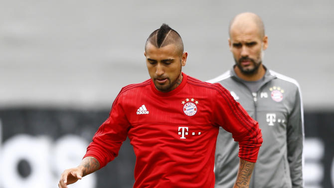 New player for Bayern Munich, Chile's Arturo Vidal, foreground, stops the ball besides coach Pep Guardiola from Spain during his first training session in Munich, Germany, on Wednesday, July 29, 2015. (AP Photo/Matthias Schrader)