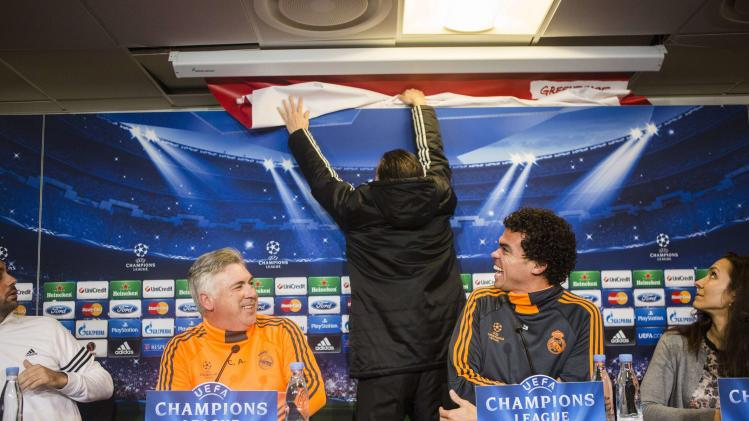 An official from FC Copenhagen removes a banner placed by Greenpeace during a news conference with Real Madrid head coach Carlo Ancelotti and Real Madrid defender Pepe at Parken stadium in Copenhagen