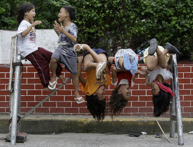 Filipino children play on steel barriers along a road in Manila, Philippines on Saturday Aug. 6, 2011. (AP Photo/Aaron Favila)