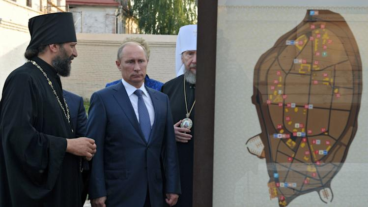 Russian President Vladimir Putin, center, flanked by Orthodox priests, visits a historical and architectural museum in Bolgar, about 700 kilometers (450 miles) east of Moscow, central Russia, Tuesday, Aug. 28, 2012. (AP Photo/RIA-Novosti, Alexei Nikolsky, Presidential Press Service)