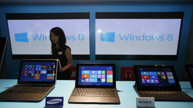 FILE - In this Friday, Oct. 26, 2012, file photo, a woman walks past laptop computers running Microsoft Windows 8 operating system during its launching ceremony in Hong Kong. Research firm IDC says PC global shipments of PCs fell 14 percent in the first three months this year. The appeal of tablets and smartphones is pulling money away from PC sales, but it also blames Microsoft's latest version of Windows, which forces users to learn new ways to control their machines. (AP Photo/Kin Cheung, File)