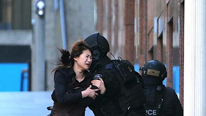 In this Dec. 15, 2014 photo, a hostage runs to armed tactical response police officers for safety after she escaped from a cafe under siege at Martin Place in the central business district of Sydney, Australia. New South Wales state police would not say what was happening inside the cafe or whether hostages were being held. But television footage shot through the cafe's windows showed several people with their arms in the air. (AP Photo/Rob Griffith)