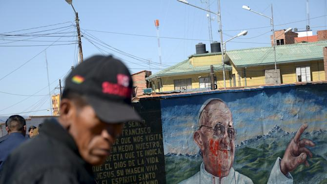 A man is seen next to a damaged mural of Pope Francis in El Alto, on the outskirts of La Paz