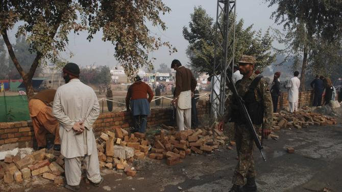 Soldier from the Pakistan Army walks past labourers working to build a wall around the Army Public School, which was attacked by Taliban gunmen, in Peshawar