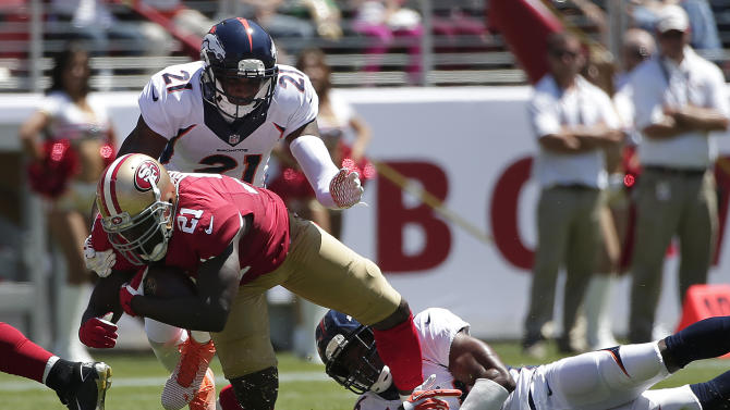 San Francisco 49ers running back Frank Gore, bottom left, is tackled by Denver Broncos cornerback Aqib Talib, top, and free safety Rahim Moore during the first quarter of an NFL preseason football game in Santa Clara, Calif., Sunday, Aug. 17, 2014. (AP Photo/Marcio Jose Sanchez)