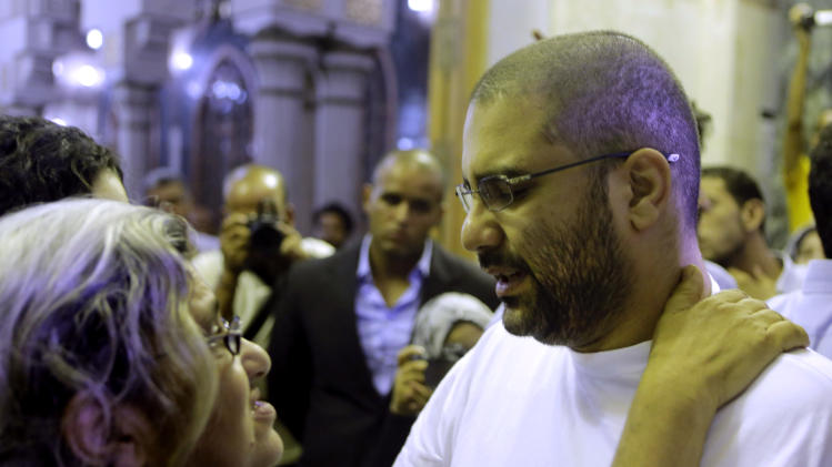 Prominent Egyptian blogger Alaa Abdel-Fattah hugs his mother, Laila Soueif, a university professor who is an also an activist, as he receives condolences for his father Ahmed Seif at Omar Makram mosque in Cairo, Egypt, Saturday, Aug. 30, 2014. Seif, one of Egypt's most prominent civil rights lawyer and campaigner who defended Islamists, atheists and homosexuals alike and worked to hold Egypt's decades-old police state accountable for torture and abuse, died Wednesday. Among Seif's last clients was his son, Abdel-Fattah, who was sentenced to 15 years for violating a controversial protest law. Seif's younger daughter Sana Seif is also being detained and on trial for protesting. (AP Photo/Amr Nabil)