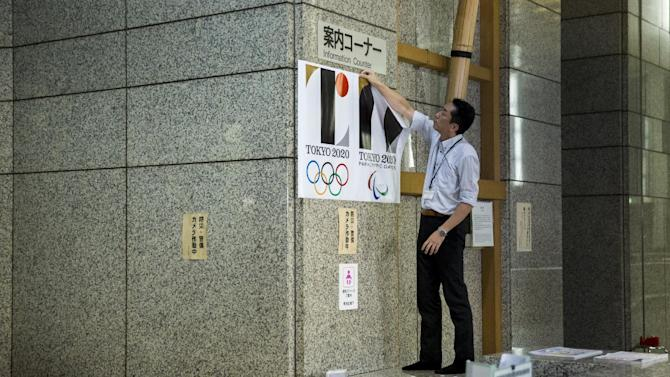 An employee takes down a placard with the Tokyo 2020 Olympic Games emblem during a staged event for the media at the Tokyo Metropolitan Government Building in Tokyo