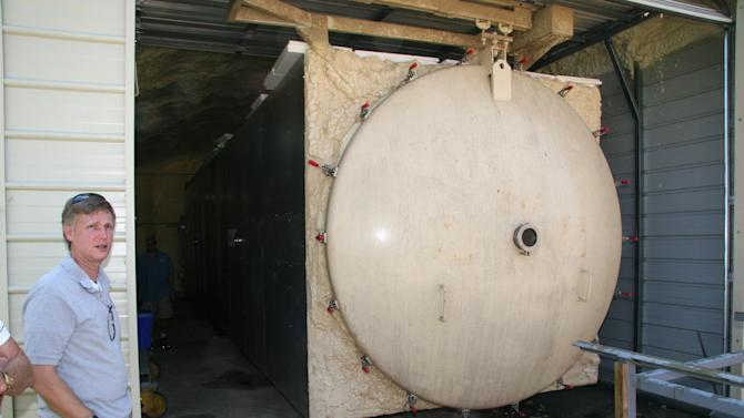 In this Aug. 8, 2012, photo Peter Fix, a conservator,  stands outside a 40-foot-long, 8-feet-wide freeze dryer at the Texas A&M University Center for Maritime Archaeology and Conservation in Bryan, Texas. The freeze-dryer is being used to remove moisture from the wreckage of a 17th-century French ship used by famed explorer La Salle and sank more than 300 years ago off the Texas coast. The ice comes from water removed from the timber of the disassembled shipwreck that's being subjected to months of controlled environment under temperatures reaching 60 below zero. The freeze-dried wood will be used in reconstruction of the nearly 60-foot ship at a state history museum in Austin. (AP Photo/Michael Graczyk)