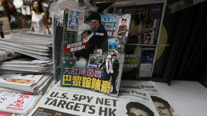 The picture of Edward Snowden, bottom, former CIA employee who leaked top-secret documents about sweeping U.S. surveillance programs, is displayed on the front page of South China Morning Post at a news stand in Hong Kong Thursday, June 13, 2013. Snowden dropped out of sight after checking out of a Hong Kong hotel on Monday. The South China Morning Post newspaper said it was able to locate and interview him on Wednesday. It provided brief excerpts from the interview on its website. (AP Photo/Kin Cheung)
