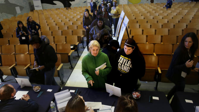 "Parents of school children, including Victoria Petronio, center, line up to collect relief funds at a school auditorium in the Rockaways section of New York, Thursday, Jan. 10, 2013. The New York City financial services firm that lost the most workers in the Sept. 11 terror attacks announced that it will ""adopt"" 19 schools in communities hit hard by Superstorm Sandy and give a total of $10 million to families in those schools. (AP Photo/Seth Wenig)"