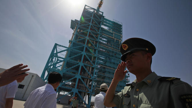 A Chinese soldier salutes near the Shenzhou 9 spacecraft rocket launch pad at the Jiuquan Satellite Launch Center near Jiuquan in western China's Gansu province, Saturday, June 16, 2012. China will send its first woman and two other astronauts into space Saturday to work on a temporary space station for about a week, in a key step toward becoming only the third nation to set up a permanent base in orbit. (AP Photo/Ng Han Guan)