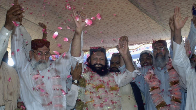 FILE - In this July 15, 2011, file photo, Malik Ishaq, center, a leader of the banned Sunni Muslim group Lashkar-e-Jhangvi, and his colleagues, raise hands in response their supporters who greeted him with rose-petals upon his arrival at his hometown in Rahim Yar Khan, Pakistan, after his release from jail. Ishaq, one of Pakistan's most-feared Islamic militant leaders, believed to be behind the killing of scores of minority Shiites, was gunned down along with 13 associates during a militant assault on a police convoy that was transporting him from prison on Wednesday. (AP Photo/Khalid Tanveer, File)