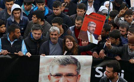 People hold portraits of Bar Association President Tahir Elci as they march during his funeral in Kurdish dominated southeastern city of Diyarbakir