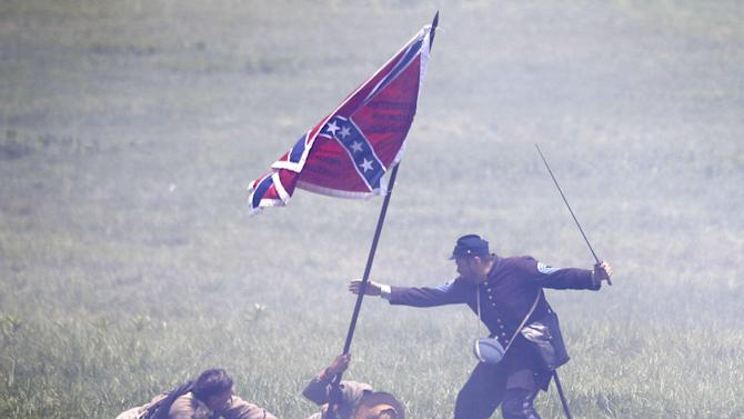 William H. Hincks, right, portrays his great, great, grandfather Medal of Honor recipient William Bliss Hincks taking a Confederate flag from a color bearer portrayed by Skip Koontz, center, of Sharpsburg Md., at a re-enactment of Pickett's Charge during ongoing activities commemorating the 150th anniversary of the Battle of Gettysburg, Sunday, June 30, 2013, at Bushey Farm in Gettysburg, Pa. Union forces turned away a Confederate advance in the pivotal battle of the Civil War fought July 1-3, 1863, which was also the war's bloodiest conflict with more than 51,000 casualties. (AP Photo/Matt Rourke)