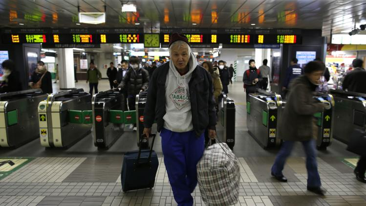 Shizuya Nishiyama, a 57-year-old homeless man from Hokkaido, poses for a photo in front of an automatic ticket barrier at Sendai Station in Sendai, northern Japan
