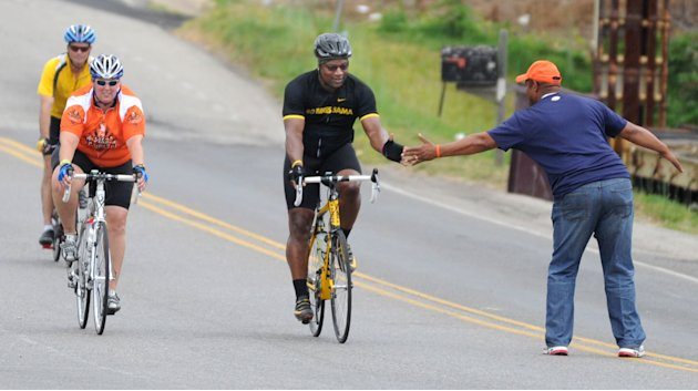 Bo Jackson greets a fan as he pedals to Jack's restaurant in Pleasant Grove, Ala., Friday, April 27, 2012,,  on the fourth day of the Bo Bikes Bama charity bike ride on the one-year anniversary of the