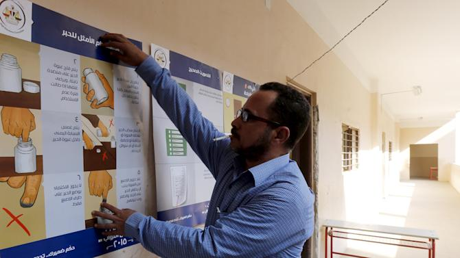 An elections committee staff member puts up posters with information for voters at a school used as a polling station during the second phase of the parliamentary election runoff in Toukh