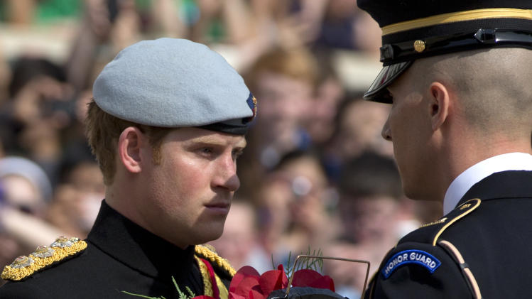 Britain's Prince Harry accepts a wreath from a member of The Old Guard during a wreath laying ceremony at the Tomb of the Unknowns at Arlington National Cemetery in Arlington, Va Friday, May 10, 2013. (AP Photo/Carolyn Kaster)