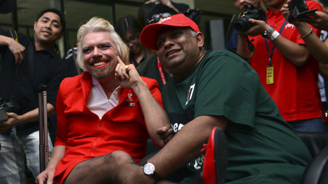 British entrepreneur Richard Branson, left, poses with AirAsia's Chief Executive Tony Fernandes while dressed up as an AirAsia flight attendant at a low cost carrier terminal in Malaysia, Sunday, May 12, 2013.  Branson wore the costume after losing a bet with his friend Fernandes on which of their 2010 Formula One racing car teams would finish ahead of the other. (AP Photo/Vincent Thian)