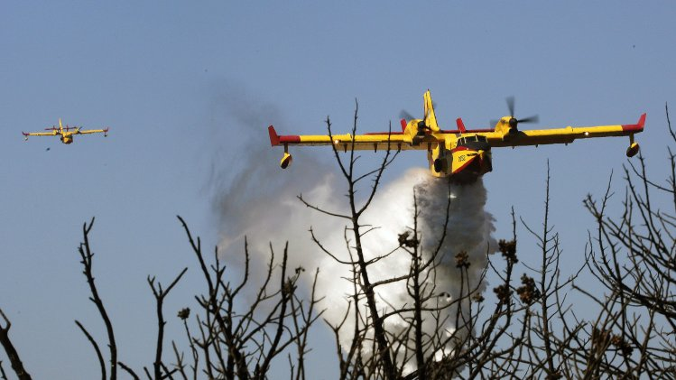 A firefighting aircraft drops water over a forest fire in Marathon near Athens