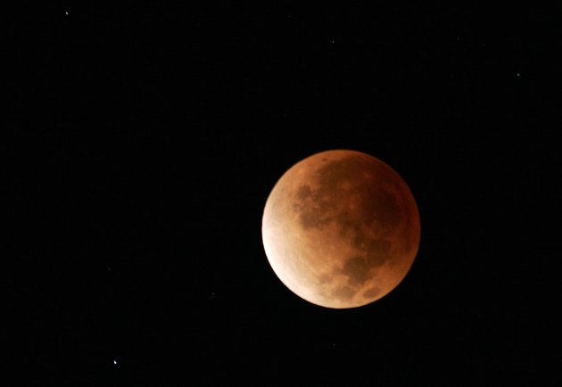 The lunar eclipse sets over the North Shore of Oahu in Haleiwa, Hawaii.