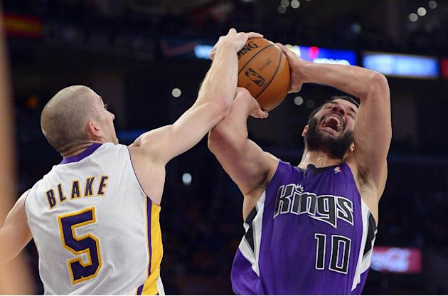 Los Angeles Lakers guard Steve Blake, left, blocks the shot of Sacramento Kings guard Greivis Vasquez, of Venezuela, during the second half of an NBA basketball game Sunday, Nov. 24, 2013, in Los Ange