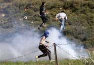 Stone-throwing Palestinian protesters run away from tear gas fired by Israeli security forces during clashes in the West Bank village of Kusra, near Nablus February 23, 2013. A Palestinian man was shot in the stomach on Saturday when clashes broke out in the occupied West Bank between Jewish settlers, Palestinians and Israeli soldiers, a medical official and military sources said. REUTERS/Abed Omar Qusini