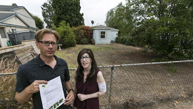 Michael Korte and his wife Laura Whitney, pose outside their home lawn in Glendora, Calif., Thursday, July 17, 2014. The Southern California couple who scaled back watering due to drought received a letter from the city of Glendora warning that they could face fines if they don't get their brown lawn green again. They are told if they don't revive the lawn they could be hit with up to $500 in fines and possible criminal action. City Manager Chris Jeffers says the couple has not been cited and called it a friendly letter prompted by a neighbor's complaint. (AP Photo/Damian Dovarganes)