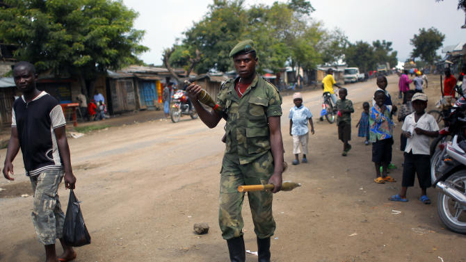 FILE -  In this Aug. 5, 2012 file photo, an M23 rebel walks the streets of the North Kivu town of Rubare near Rutshuru, 75 km (48 miles) north of Goma, Congo. The Rwandan-backed rebel group advanced to within 4 kilometers (2.4 miles) of Goma, a crucial provincial capital in eastern Congo, marking the first time that rebels have come this close since 2008. Congolese army spokesman Col. Olivier Hamuli said the fighting has been going on since 6 a.m. Sunday, Nov. 18, 2012, and the frontline has moved to just a few kilometers (miles) outside the city.(AP Photo/Jerome Delay, File)