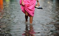 A student wades through a flooded street after a heavy rain caused by typhoon Nock-ten in San Juan city, east of Manila on July 26, 2011. The death toll from tropical storm Nock-ten climbed to 41 on Friday
