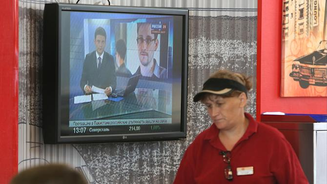An airport worker passes a TV screen with a news program showing a report on Edward Snowden at Sheremetyevo,airport in Moscow Wednesday, June 26, 2013. Russia's President Vladimir Putin said Tuesday that National Security Agency leaker Edward Snowden has remained in Sheremetyevo's transit zone, but media that descended on the airport in the search for him couldn't locate him there.(AP Photo/Sergei Grits)