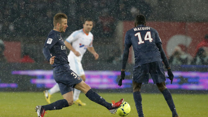 Paris Saint Germain's David Beckham, left,  runs with the ball  during the League One soccer match between PSG and Marseille at Parc des Princes Stadium, in Paris, Sunday Feb. 24, 2013. Beckham made his Paris St Germain debut as Carlo Ancelotti's men took a potentially vital step towards claiming the Ligue 1 title. (AP Photo/Francois Mori)