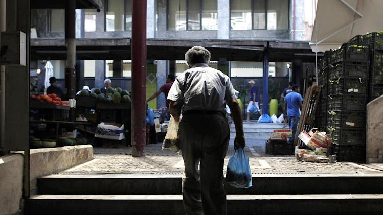 An elderly man carries shopping bags at Athens' central fruit and vegetable market, on Tuesday, Aug. 13, 2013. Greece is beating its budget targets by a wide margin so far this year, a sign the country's painful cost cuts and tax increases, combined with international bailout funds, are paying off.(AP Photo/Petros Giannakouris)