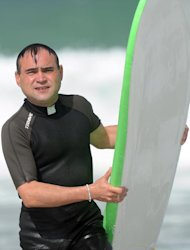 French Catholic priest Rene-Sebastien Fournie comes out of the water after surfing at Bidart, southwestern France, on September 3, 2013