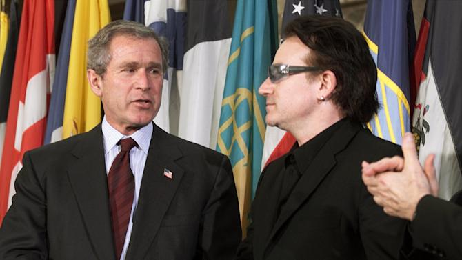 FILE - This is a  Thursday, March 14, 2002 file photo of  President Bush as he shakes hands with Bono, right, lead singer of the Irish rock group U2, after Bush spoke at the Inter-American Development Bank,  in Washington.  (AP Photo/Ron Edmonds)