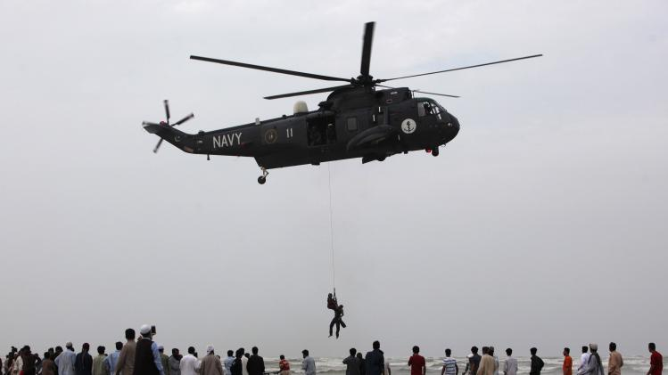 People gather as a Pakistan Navy diver attached to a sling rope from a helicopter, holds the body of a man who had drowned on Wednesday, after recovering it from Arabian Sea during a search rescue operation at Karachi's Clifton beach