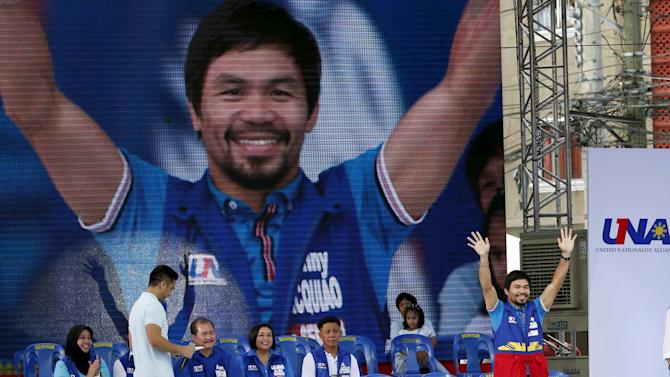 Filipino boxer Manny Pacquiao, who is running for senator, waves to supporters during the start of campaigning for the national elections in Mandaluyong city, Metro Manila
