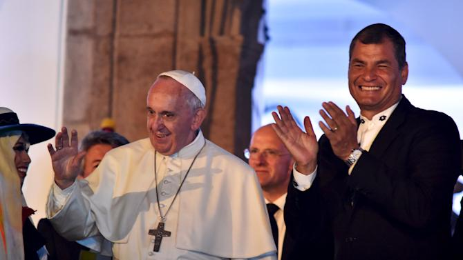 Pope Francis waves next to Ecuador's President Rafael Correa in Quito