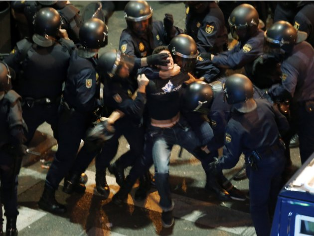 A demonstrator struggles with Spanish National Police riot officers outside the the Spanish parliament in Madrid